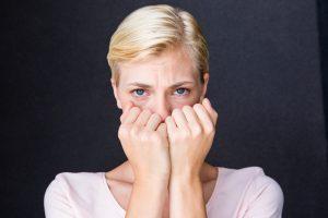 womancoveringfaceblond