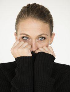womancoveringmouthblksweater